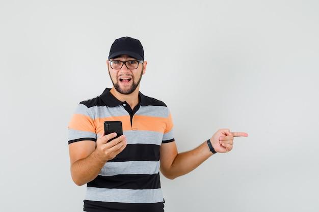 Jovem, segurando o telefone celular, apontando para o lado na camiseta, boné e olhando positiva, vista frontal.