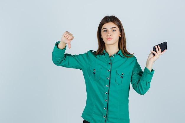 Jovem, segurando o telefone celular, mostrando o polegar para baixo na camisa verde e parecendo descontente, vista frontal.