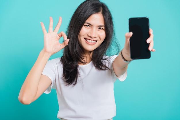 Jovem, segurando o telefone móvel e mostrando o gesto ok