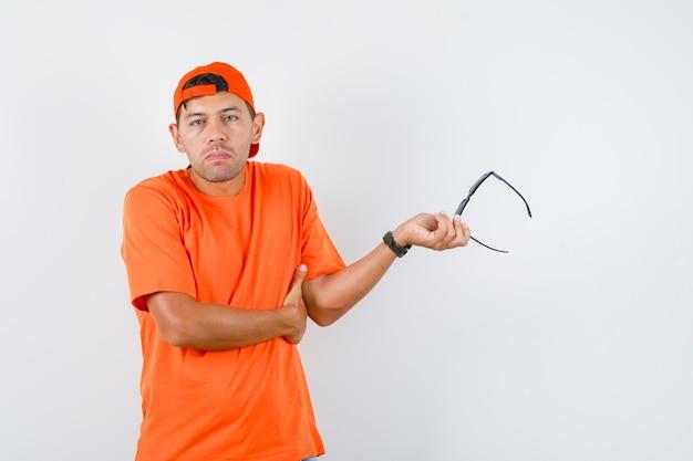 Jovem segurando óculos em uma camiseta laranja e boné e parecendo confuso