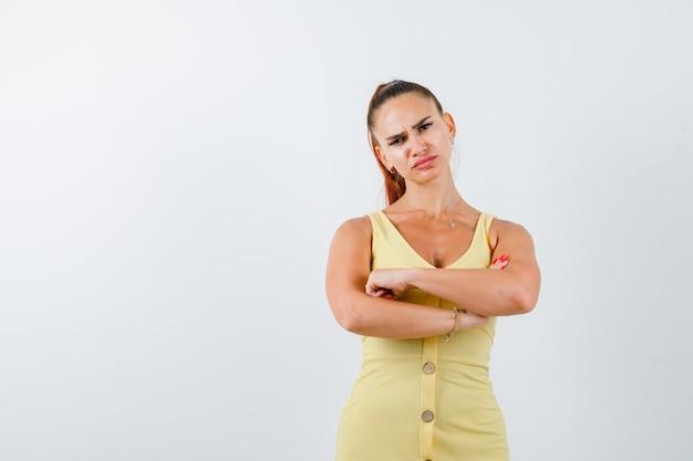 Jovem, segurando os braços cruzados em um vestido amarelo e parecendo decepcionada, vista frontal.
