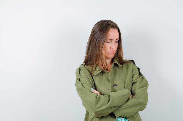 Jovem, segurando os braços cruzados, olhando para longe na jaqueta verde e parecendo chateada, vista frontal.