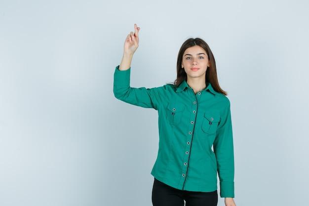 Jovem, segurando os dedos cruzados na blusa verde, calça preta e parecendo feliz. vista frontal.