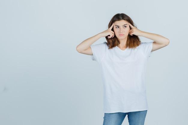 Jovem, segurando os dedos na cabeça em uma camiseta, jeans e parecendo pensativa. vista frontal.