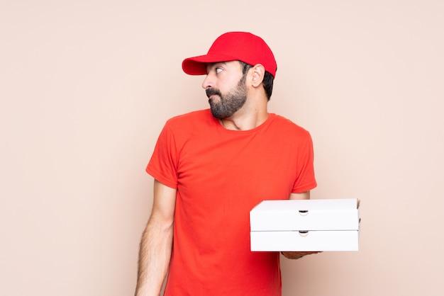 Jovem, segurando, pizza, isolado, fazendo, dúvida, gesto, olhar, lado