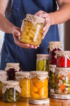 Jovem segurando potes com comida caseira em conserva e fermentada, em conserva e marinada. preservação da colheita, produtos locais dos agricultores