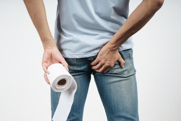 Jovem segurando seu traseiro e lenço de papel porque diarréia, hemorróidas, prisão de ventre. cuidados de saúde e conceito médico.