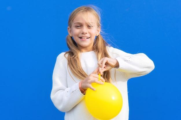 Jovem segurando um balão amarelo