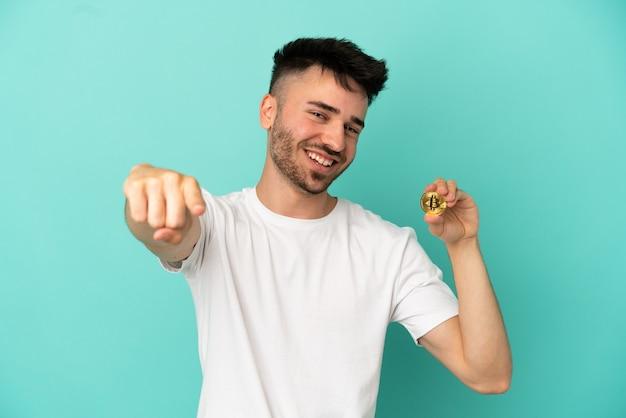 Jovem segurando um bitcoin isolado em um fundo azul apontando para a frente com uma expressão feliz