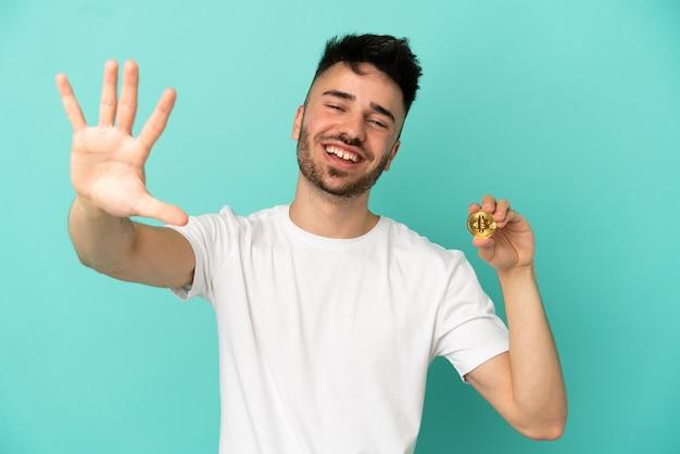 Jovem segurando um bitcoin isolado em um fundo azul, contando cinco com os dedos