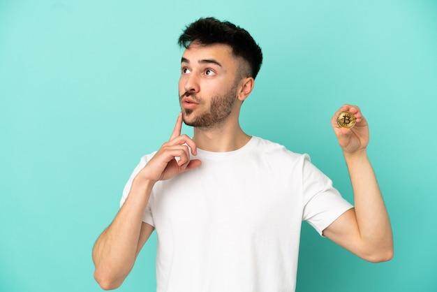 Jovem segurando um bitcoin isolado em um fundo azul, pensando em uma ideia apontando o dedo para cima