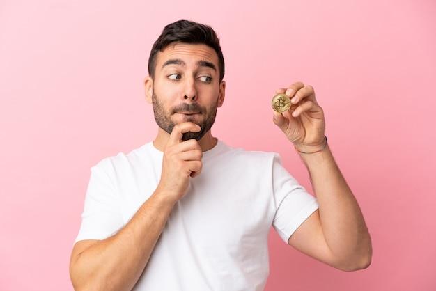Jovem segurando um bitcoin isolado em um fundo rosa, tendo dúvidas e pensando
