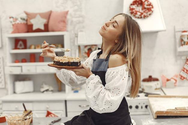 Jovem segurando um bolo caseiro na cozinha