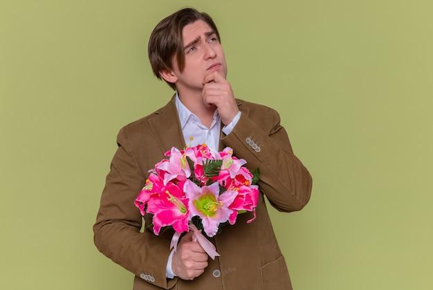 Jovem segurando um buquê de flores olhando para cima com uma expressão pensativa e pensando em parabenizar com o conceito do dia internacional da mulher em pé sobre a parede verde