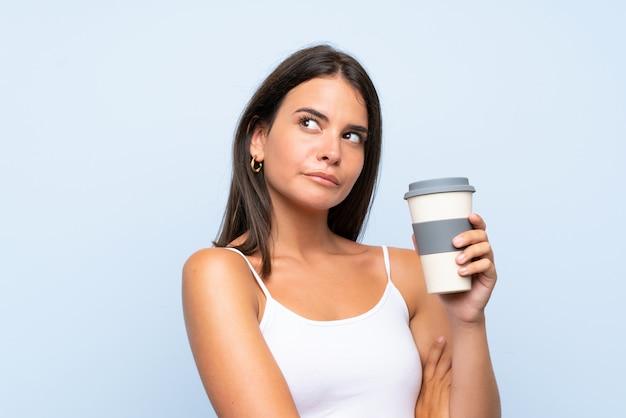 Jovem, segurando um café take away sobre parede azul isolada, fazendo dúvidas gesto enquanto levanta os ombros