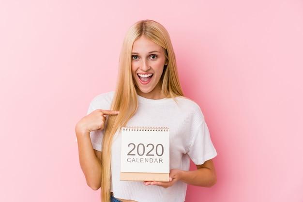 Jovem, segurando um calendário 2020 surpreendeu apontando para si mesmo, sorrindo amplamente