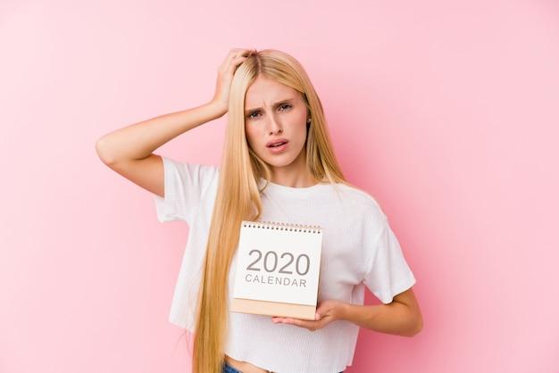 Jovem, segurando um calendário de 2020 chocada, lembrou-se de uma reunião importante.