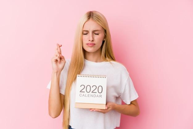 Jovem, segurando um calendário de 2020 cruzar os dedos por ter sorte