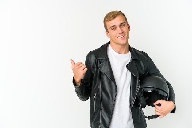 Jovem segurando um capacete de motocicleta isolado na parede branca aponta com o dedo polegar afastado, rindo e despreocupado