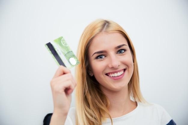 Jovem segurando um cartão do banco