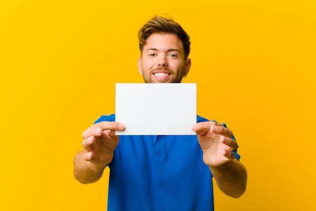 Jovem, segurando um cartaz contra fundo laranja