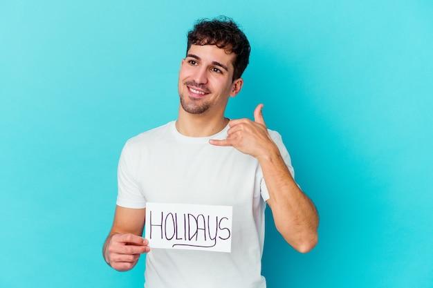 Jovem segurando um cartaz de feriados isolado, mostrando um gesto de chamada de celular com os dedos