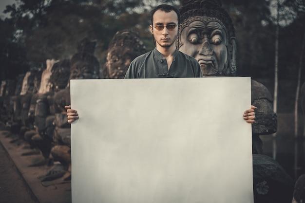 Jovem segurando um cartaz em branco em um local escuro e místico