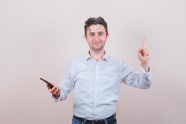 Jovem segurando um celular, apontando para cima com uma camiseta, jeans e uma expressão positiva
