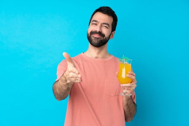 Jovem segurando um cocktail sobre parede azul isolada, apertando as mãos para fechar um bom negócio