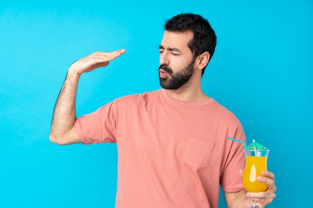 Jovem, segurando um cocktail sobre parede azul isolada com expressão cansada e doente