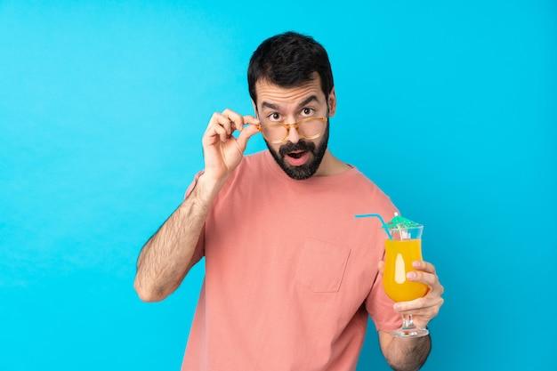 Jovem, segurando um cocktail sobre parede azul isolada com óculos e surpreso