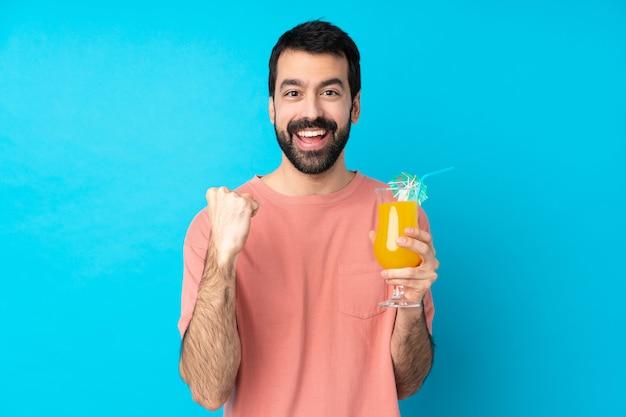 Jovem, segurando um cocktail sobre parede azul isolada, comemorando uma vitória na posição de vencedor