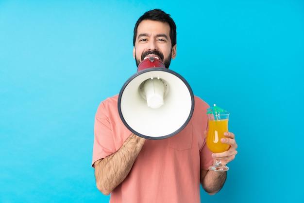 Jovem, segurando um cocktail sobre parede azul isolada, gritando através de um megafone
