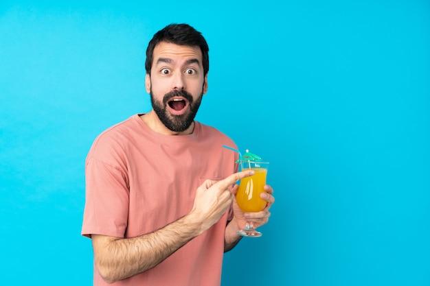 Jovem, segurando um cocktail surpreso e apontando o lado