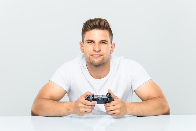 Jovem, segurando um controlador de jogo feliz, sorridente e alegre.