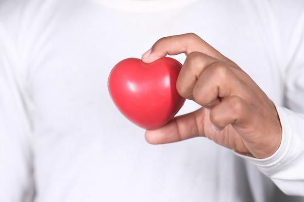 Jovem segurando um coração vermelho em branco