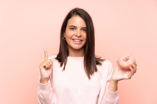 Jovem, segurando um donut sobre parede rosa isolada, apontando para cima uma ótima idéia