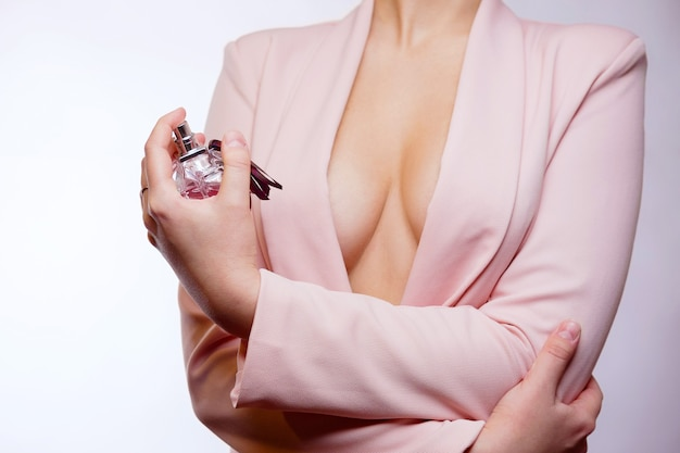 Jovem segurando um frasco de perfume na mão, casaco rosa, peito seminu