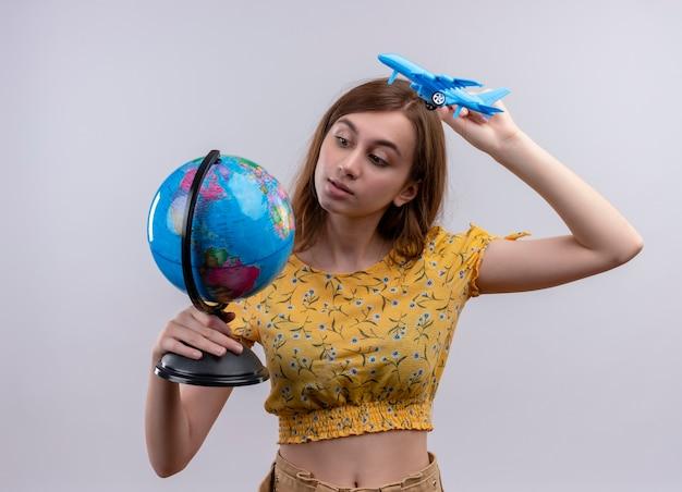 Jovem segurando um globo e um modelo de avião e olhando para o globo na parede branca isolada