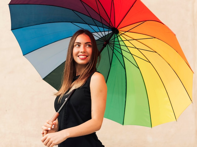 Jovem segurando um guarda-chuva arco-íris