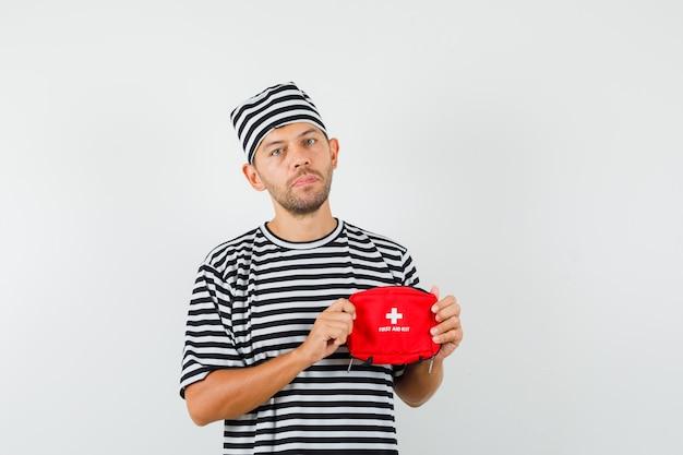 Jovem segurando um kit de primeiros socorros com um chapéu de camiseta listrada e olhando com cuidado
