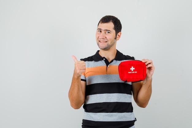 Jovem segurando um kit de primeiros socorros enquanto mostra o polegar para cima em uma camiseta e parece satisfeito