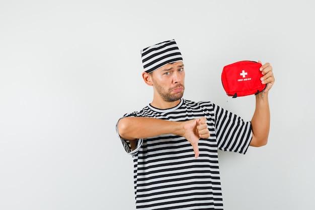Jovem segurando um kit de primeiros socorros, mostrando o polegar para baixo com um chapéu de camiseta listrada e parecendo desapontado