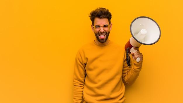 Jovem, segurando um megafone funnny e língua mostrando amigável