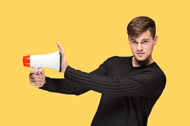 Jovem segurando um megafone no fundo amarelo do estúdio