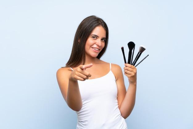 Jovem, segurando um monte de pincel de maquiagem aponta o dedo para você com uma expressão confiante