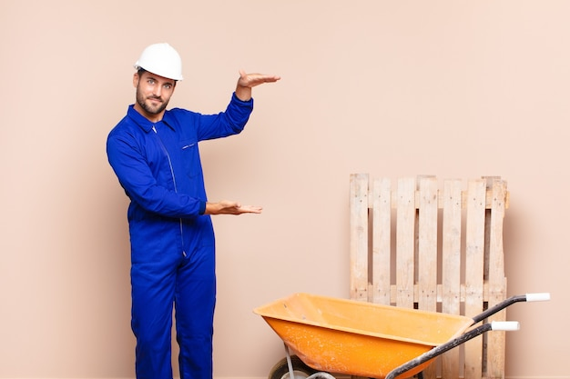 Jovem segurando um objeto com as duas mãos no espaço lateral de cópia, mostrando, oferecendo ou anunciando um conceito de construção de objeto