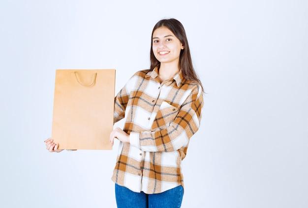 Jovem, segurando um pacote de papel artesanal e em pé sobre uma parede branca.