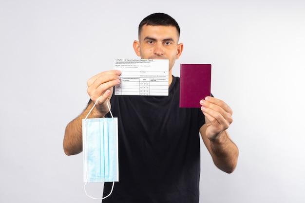Jovem segurando um passaporte com cartão de vacinação e uma máscara médica em um fundo branco e isolado