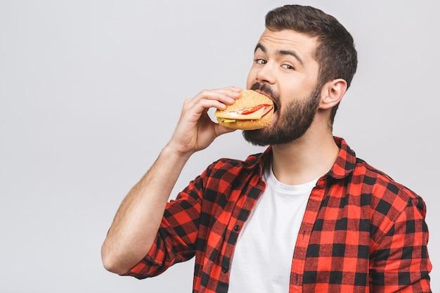 Jovem, segurando um pedaço de hambúrguer. faça dieta o conceito isolado contra o fundo branco.